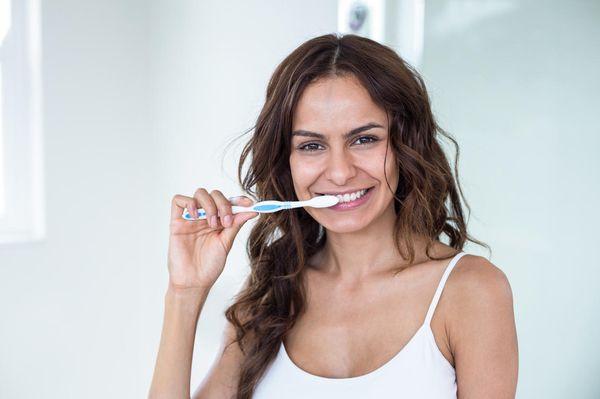 Portrait of young woman brushing teeth in bathroom