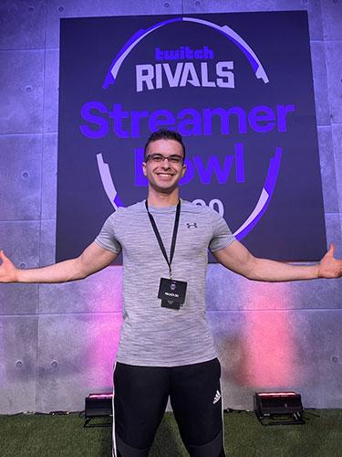 Nick Eh 30 devant une affiche des Twitch Rivals