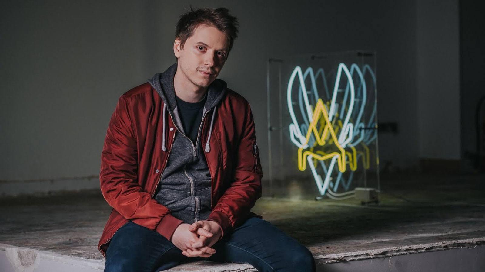 """Fabien """"Neo"""" Devide assis à côté du logo de Vitality"""