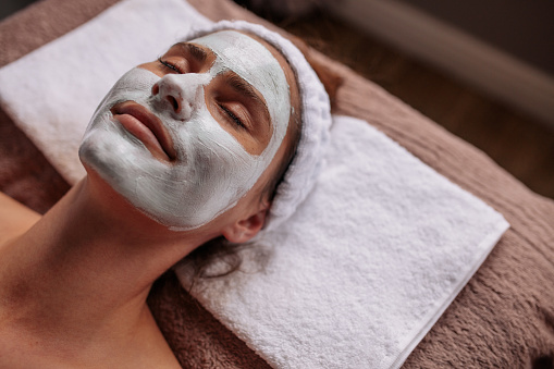 Close up of woman with cosmetic mask on her face at beauty spa