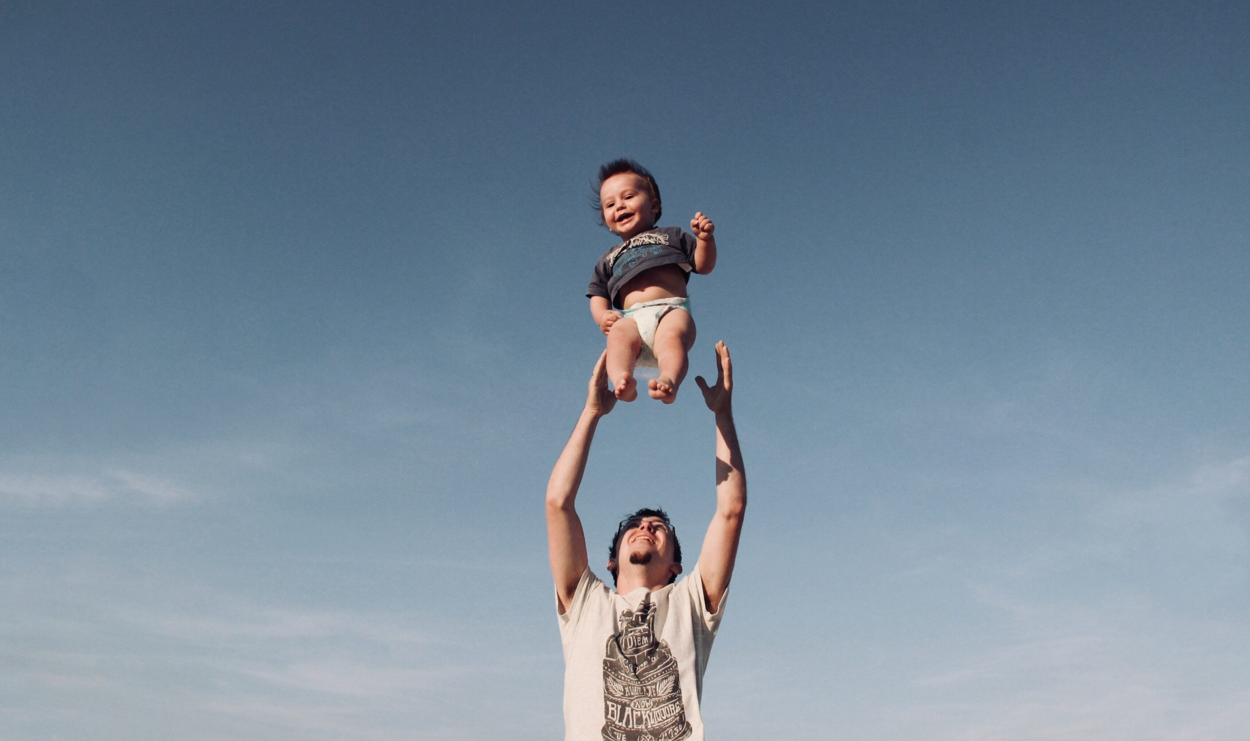 photo-of-man-in-raising-baby-under-blue-sky-1166990-scaled