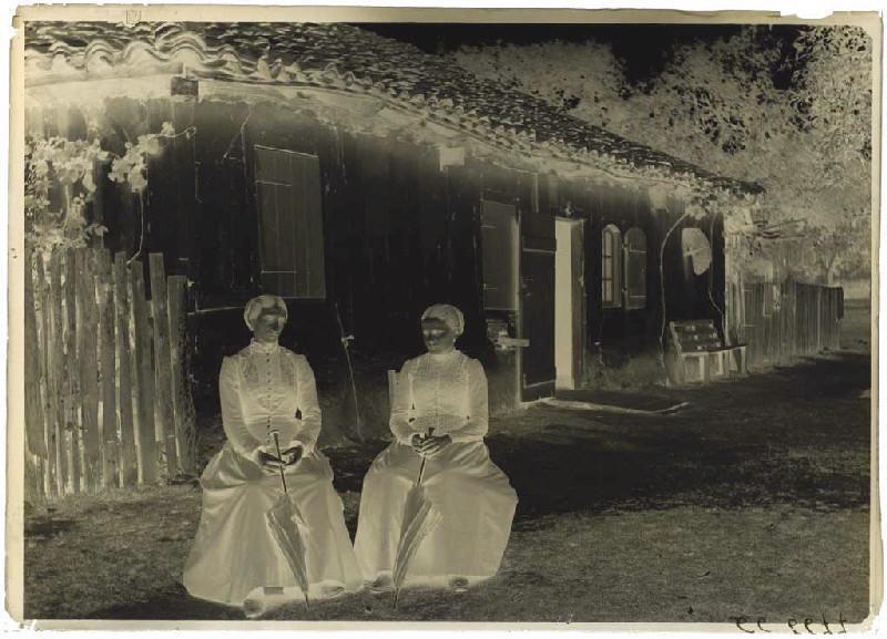 Femmes assises devant une maison_0
