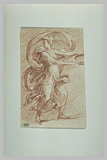 Femme debout, tournée vers la droite, tenant un crible, se retournant