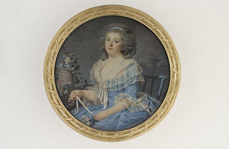 Jeune femme attachant un bouquet de fleurs