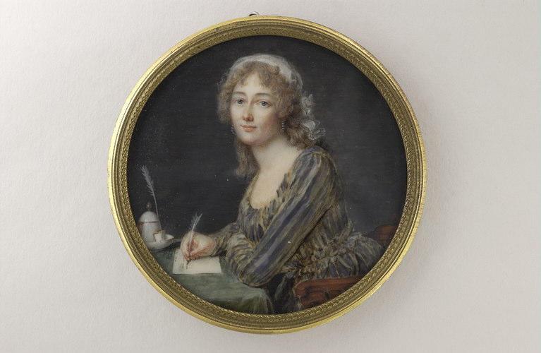 Femme écrivant, assise devant une table