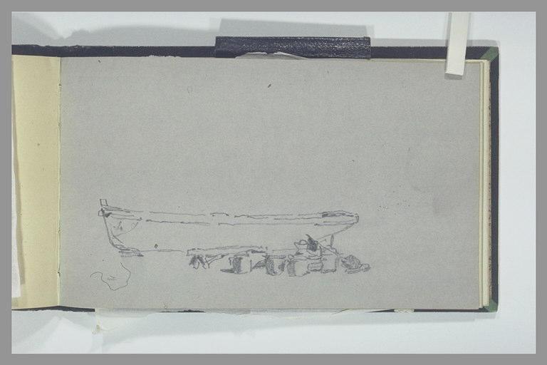 Barque sur des cales en cours de calfatage ou de peinture