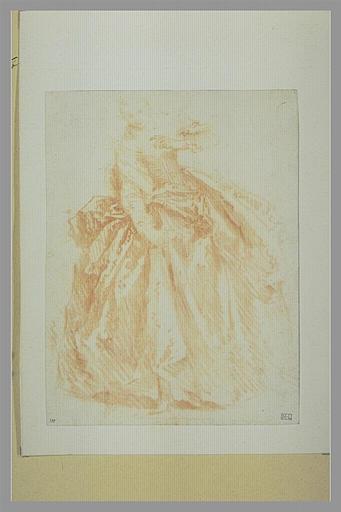 Femme, debout, le buste incliné, relevant sa robe de la main droite