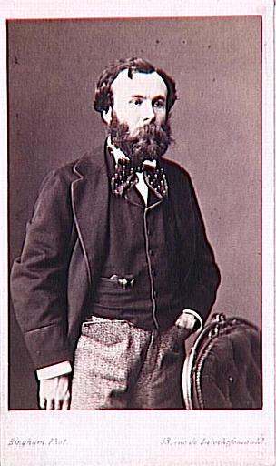 Portrait de Gustave Moreau debout, coupé à mi-jambe, derrière un fauteuil