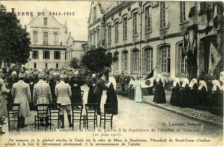Guerre 1914-1915 - Le Général Jullien remettant la Croix de guerre à la Supérieure de l'Hôpital de Soissons (10 juin 1915). Au moment où le général attache la Croix sur la robe de Madame la Supérieure, l'étendard du Sacré-Coeur s'incline saluant à la fois le dévouement récompensé et la reconnaissance de l'armée_0