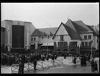 Exposition internationale ; pavillon d'exposition ; place ; façade ; personnage ; drapeau