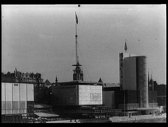 Exposition internationale ; pavillon d'exposition ; architecture métalllique ; fleuve ; personnage ; vue générale