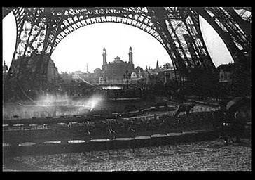 Vue d'ensemble prise au travers des pieds de la Tour Eiffel