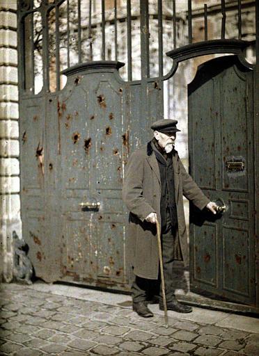 M. Reiser, habitant de Reims, se tenant à côté d'un portail endommagé par des balles