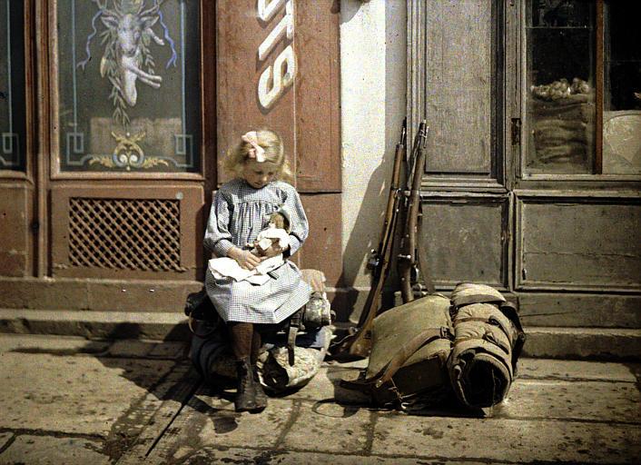 ' Petite rémoise ' : fillette jouant à la poupée dans la rue ; à côté d'elle, fusils et sac de soldat
