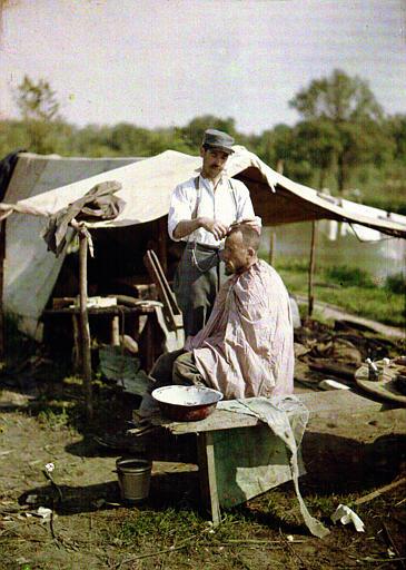 L'heure du coiffeur : dans un campement, soldat coupant les cheveux à un autre soldat