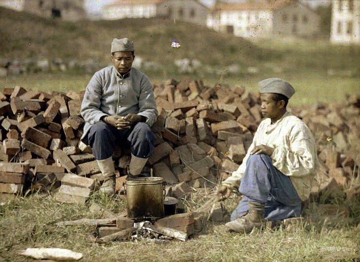 Soldats faisant leur cuisine sur un feu improvisé avec des briques et du bois (scène d'extérieur)