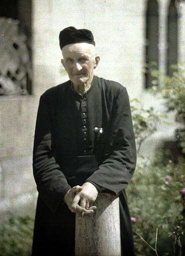 Monsieur l'abbé Hivet déblayant le jardin de l'église de Saint-Waast