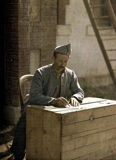 Poilu faisant sa correspondance sur une caisse en bois