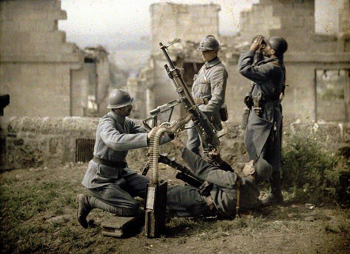 Section des mitrailleurs : quatre soldats dans les ruines, en train de tirer