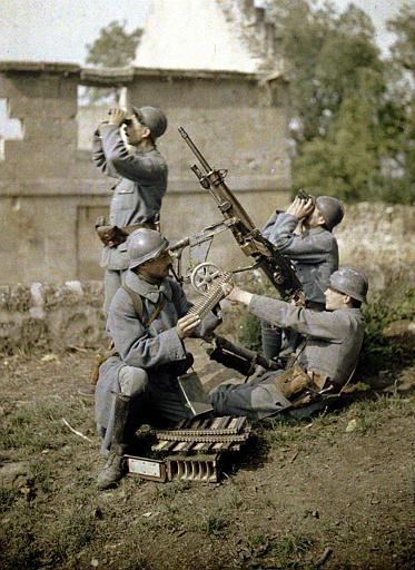 Section de mitrailleurs : quatre soldats, dans les ruines en train de tirer