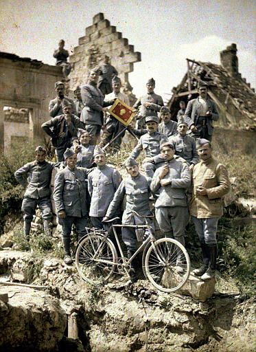 Les sous officiers du 370ème ayant subi l'attaque du 8 juillet au Chemin des Dames, posant avec une bicyclette et un drapeau de régiment. Ruines à l'arrière plan