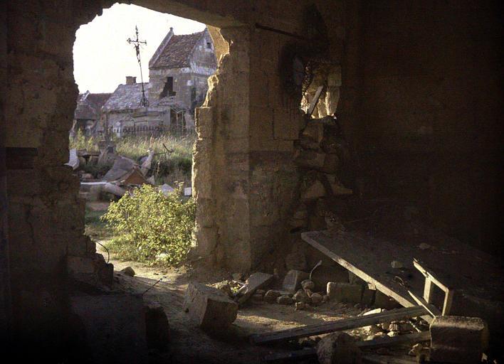 Intérieur : ruine trouée par laquelle on aperçoit des maisons