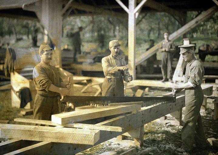 Trois canadiens au travail en train de scier des planches