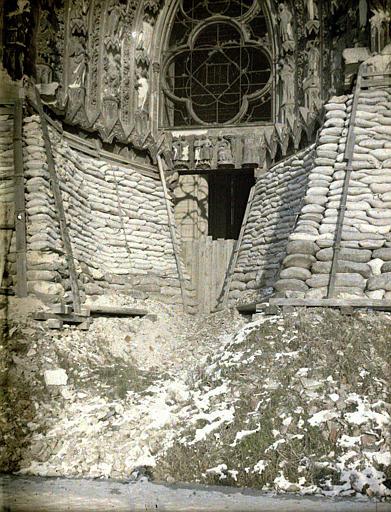 Porche gauche protégé par des planches et des sacs de sable