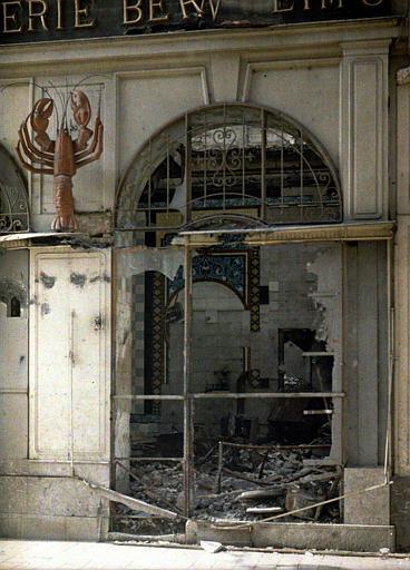 Détail de la façade : baie ouverte sur gravats et restes du décor en céramique