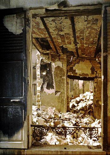 Vue prise depuis la rue par l'ouverture d'une fenêtre sur les gravats accumulés à l'intérieur d'une maison démolie