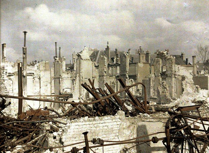 Ruines : vestiges de machines et d'installations métalliques rouillées sur fond d'immeubles détruits