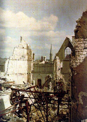 Ruines : éléments métalliques rouillées. Au deuxième plan, les vestiges d'un bâtiment religieux. Au fond, le clocher d'une église