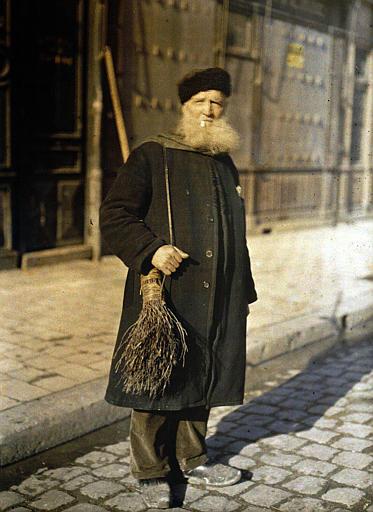 Balayeur : homme âgé à la barbe blanche portant un bonnet d'astrakan, un balai accroché à l'épaule