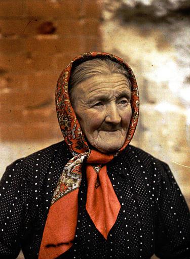 Une vieille femme avec un fichu rouge noué sous le menton