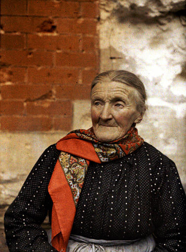 Une vieille femme avec un fichu rouge sur les épaules