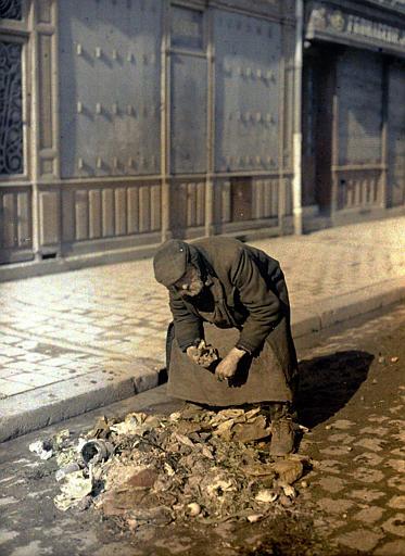 Mendiant : homme âgé cherchant parmi des débris