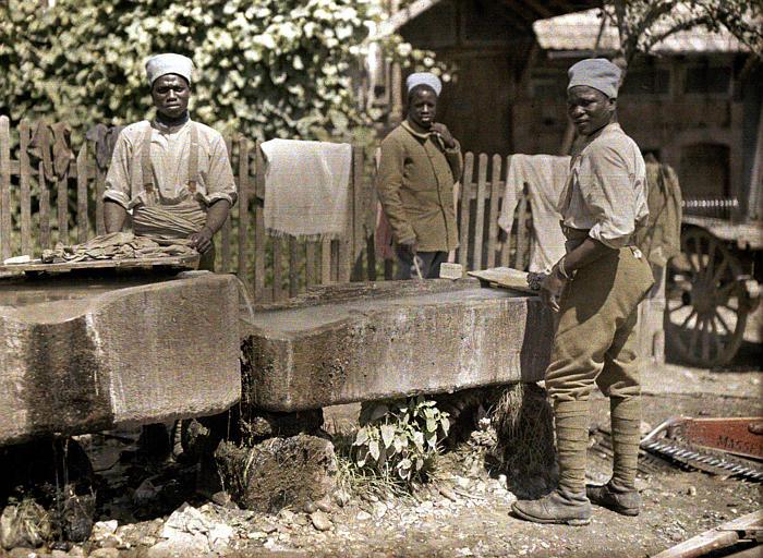 Cour de ferme : militaires sénégalais lavant le linge dans des auges