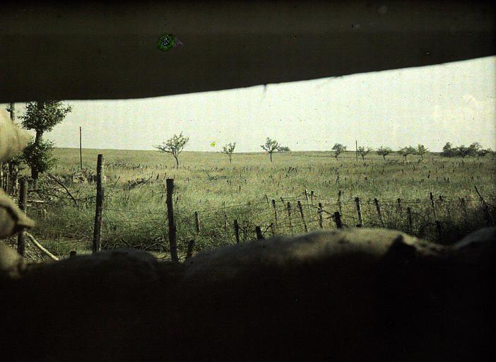 Tranchée de première ligne, poste d'observation : vue sur un champ couvert de barbelés. Au premier plan, sac de sable
