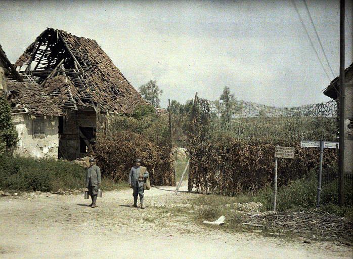 Camouflages : maison endommagée, deux poilus et des grillages garnis de verdures