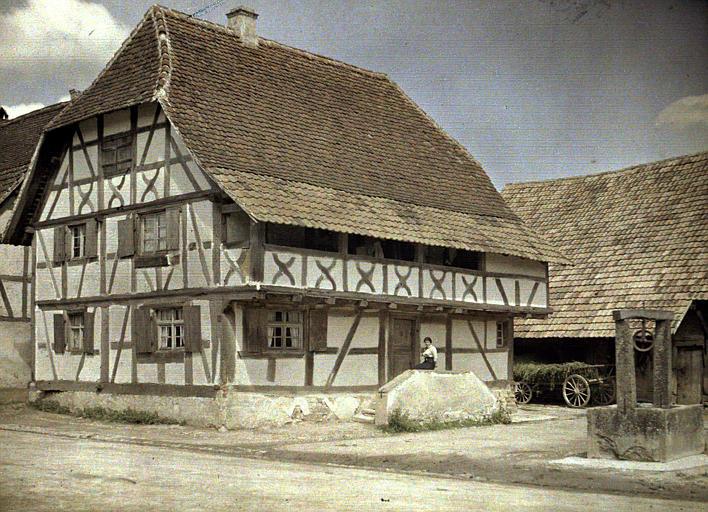 Ensemble de l'église, des maisons à pans de bois et d'un puits. Une femme assise sur le perron