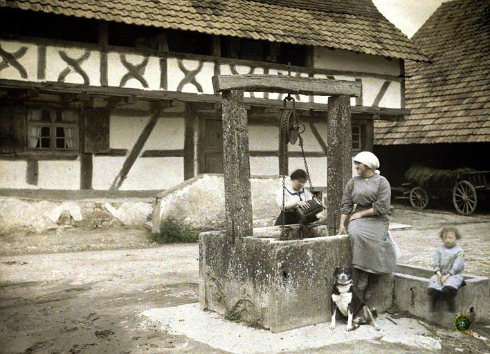 Ensemble de l'église, des maison à pans de bois : deux femmes, une fillette, un chien près d'un puits, une charrette de foin