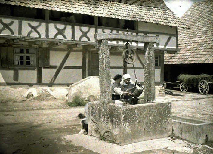 Deux femmes puisant l'eau, un chien, une charrette de foin