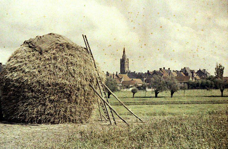 Paysage rural : une meule de paille, au fond un village