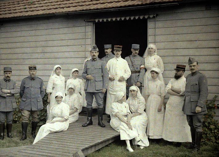 Groupe à l'hôpital 66 : infirmières, militaires, médecins devant une baraque