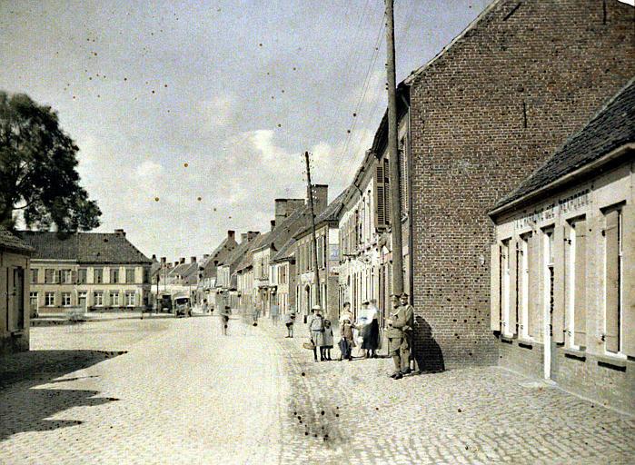 Une rue, une place : à droite le siège de l'harmonie de Rexpoede. Population civile, militaires français et alliés