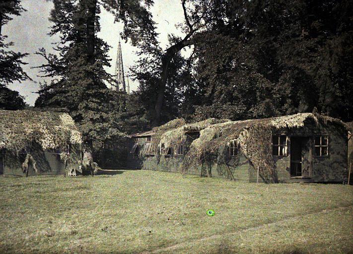 Au Q.G. : baraquements camouflés au moyen de branchages