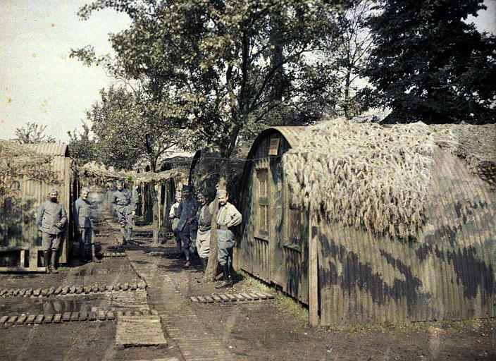 Cantonnement : baraques camouflées disposées de chaque côté d'un chemin