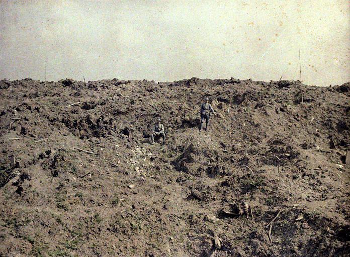 Terrain retourné par les obus : deux militaires