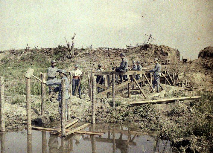 Construction d'une passerelle sur les trous d'obus, terrain retourné par les obus, trous d'obus remplis d'eau