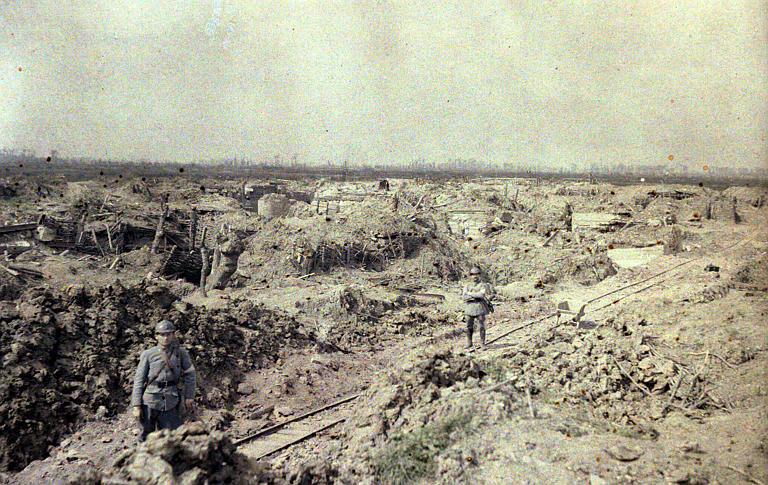 Lignes française au Het Sas ; terrain labouré par les bombardements, deux militaires, voie ferre étroite decauville